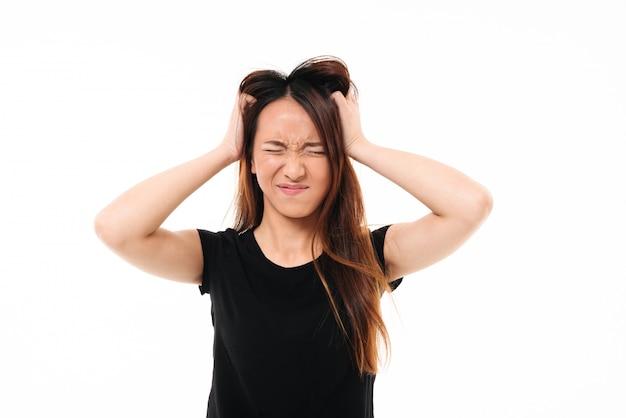Retrato do close-up da mulher asiática irritada com os olhos fechados, segurando sua cabeça