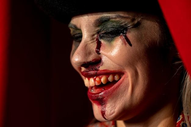 Retrato do close-up da mulher de palhaço de lado com os olhos fechados