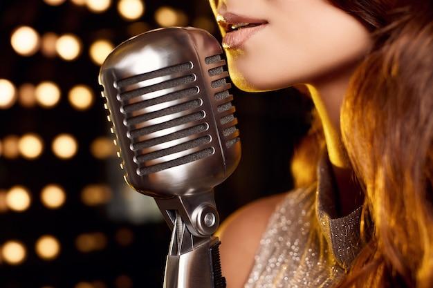 Retrato do close-up da mulher linda cantora em um vestido elegante com microfone retrô nos refletores do palco do restaurante.