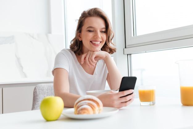Retrato do close-up da mulher morena feliz usando telefone celular enquanto tomando café na cozinha branca