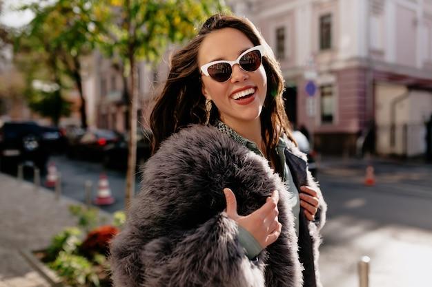 Retrato do close-up da mulher morena rindo com casaco de pele cinza rindo no fundo da cidade.