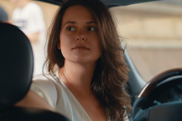 Retrato do close-up da mulher segurando a mão no volante