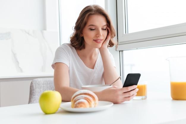 Retrato do close-up da mulher sorridente youn em camiseta branca, verificando notícias no celular enquanto está sentado e tomando café da manhã na mesa da cozinha