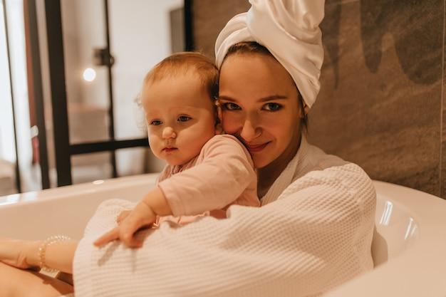 Retrato do close-up da senhora com manto branco e toalha na cabeça, sentada com a filha na banheira branca profunda.