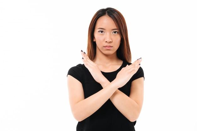 Retrato do close-up da séria jovem asiática mostrando o gesto de parada com as mãos cruzadas, olhando para a câmera