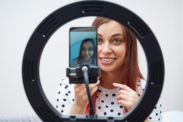 Retrato do close-up da transmissão ao vivo do blogueiro de mulher bonita usando um smartphone moderno, lâmpada de anel.