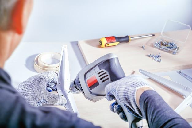 Retrato do close up das mãos masculinas que fazem a mobília na oficina dos carpinteiros. montagem de móveis.