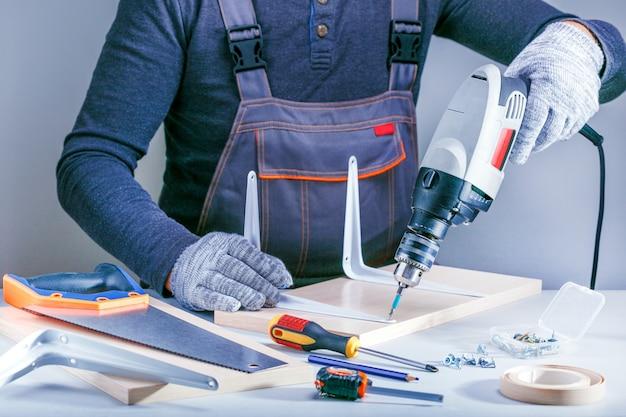 Retrato do close up das mãos masculinas que fazem a mobília na oficina dos carpinteiros.