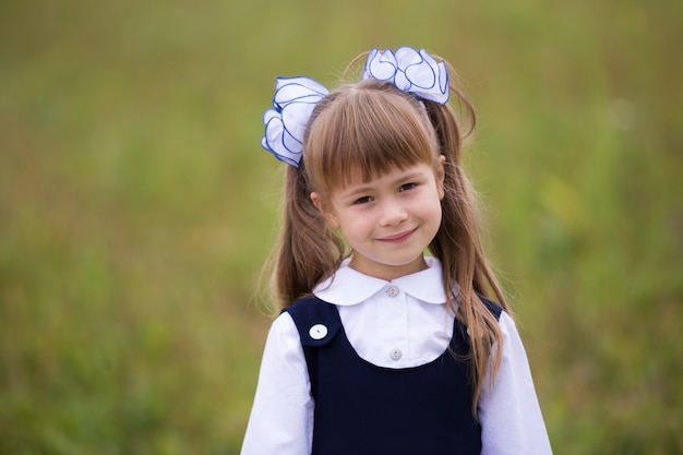Retrato do close-up de adorável adorável sorridente menina da primeira série em arcos de uniforme escolar e branco