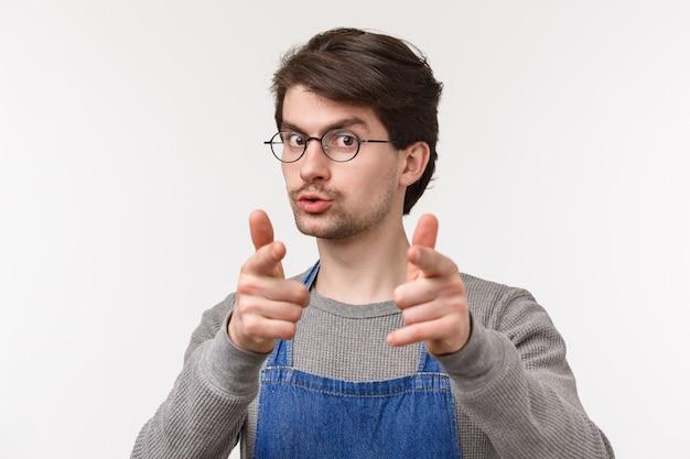 Retrato do close-up de alegre barista masculino amigável, proprietário de café convidar clientes a visitar sua loja e experimentar as melhores bebidas de sempre, apontando pistolas de dedo, parede branca de pé