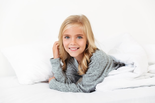 Retrato do close-up de alegre menina deitada na cama,