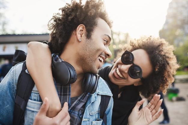 Retrato do close-up de alegre mulher de pele escura abraçando o namorado pelas costas enquanto caminhava no parque e conversava, sorrindo para ele.