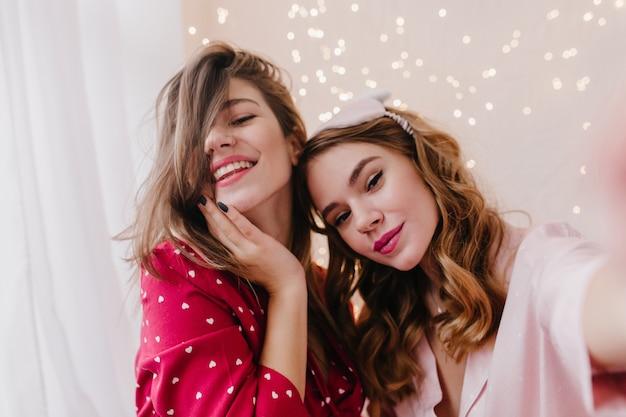 Retrato do close-up de atraente mulher encaracolada fazendo selfie com a amiga. foto interna de garotas despreocupadas tirando fotos de si mesmas.