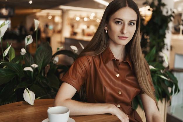 Retrato do close-up de elegante encantadora jovem encostado em uma mesa de centro em um café.