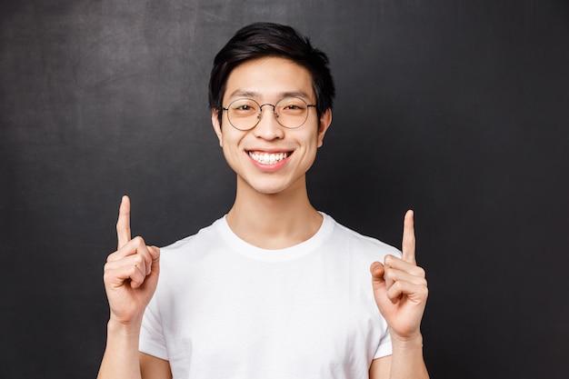 Retrato do close-up de feliz, alegre estudante do sexo masculino asiático falando sobre sua experiência de estudar no exterior, apontando os dedos para cima na apresentação, sorrindo satisfeito e despreocupado