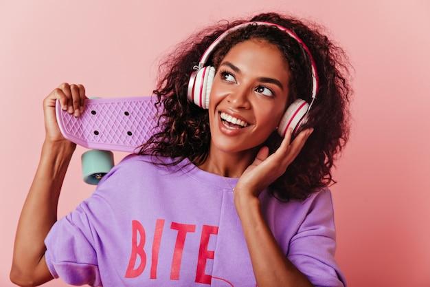 Retrato do close-up de feliz linda garota africana em fones de ouvido grandes. modelo feminino alegre com skate posando com um sorriso rosa.