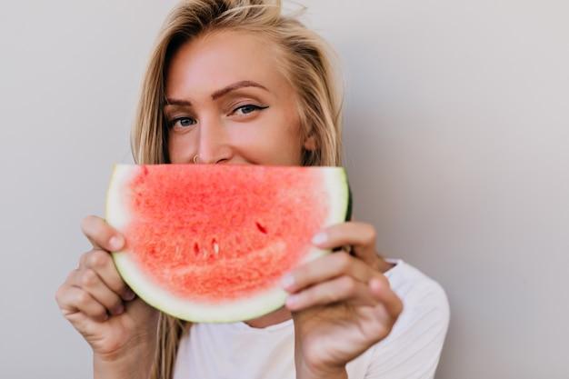 Retrato do close-up de feliz mulher caucasiana comendo frutas. foto interna de adorável mulher loira brincando na luz de fundo.