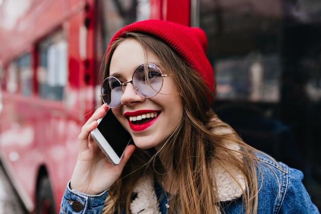 Retrato do close-up de incrível jovem com chapéu vermelho, falando no telefone na rua.