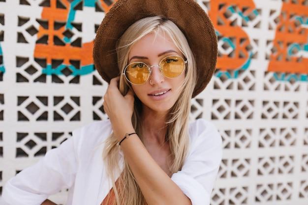 Retrato do close-up de inspirada mulher loira com cabelo comprido, posando num dia de verão. foto da bela modelo feminina interessada com chapéu marrom.