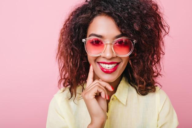 Retrato do close-up de interessada mulher negra de cabelos curtos com maquiagem da moda posando. garota atraente mulata em óculos de sol rosa e elegante camisa de algodão sorrindo.