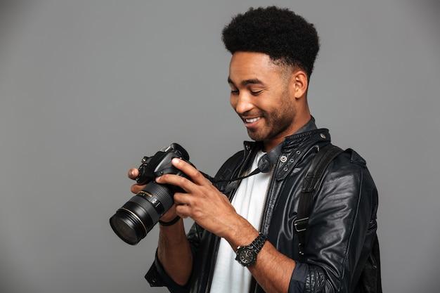 Retrato do close-up de jovem afro-americano feliz segurando e olhando para a tela da câmera de foto