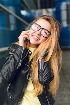 Retrato do close-up de jovem com cabelo comprido em copos do lado de fora no aeroporto. ela usa uma jaqueta preta, falando ao telefone e sorrindo