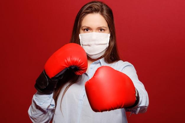 Retrato do close-up de jovem em luvas de boxe vermelhas sobre fundo vermelho na máscara médica protetora, pandemia de coronavírus, luta com vírus