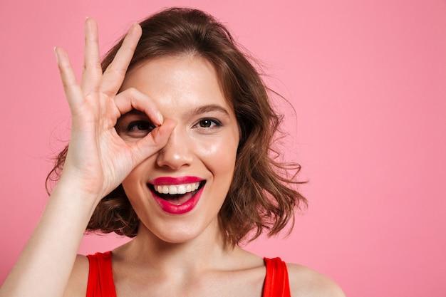 Retrato do close-up de jovem feliz com os lábios vermelhos através do sinal ok