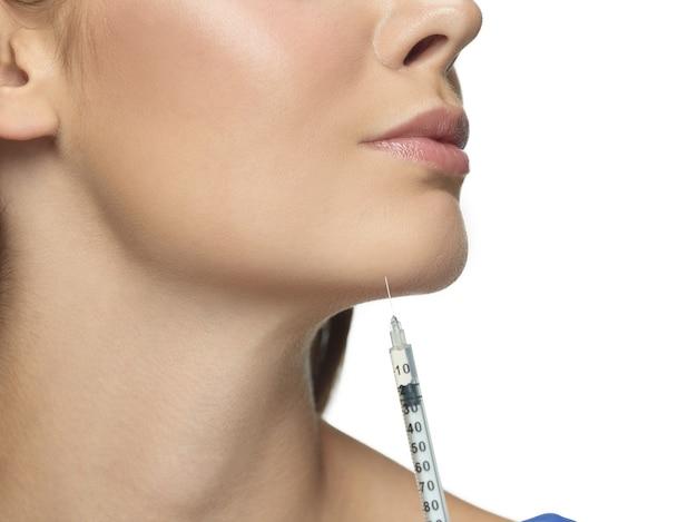 Retrato do close-up de jovem isolado na parede branca. procedimento de cirurgia de enchimento. conceito de saúde e beleza feminina, cosmetologia, autocuidado, cuidados com o corpo e a pele. anti-envelhecimento.