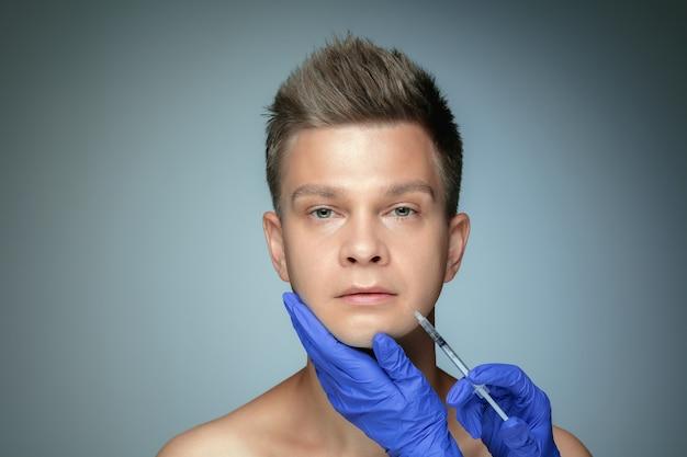 Retrato do close-up de jovem isolado na parede cinza do estúdio. procedimento de cirurgia de preenchimento, lábios e maçãs do rosto.