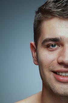 Retrato do close-up de jovem isolado no fundo cinza do estúdio. modelo masculino caucasiano, olhando para a câmera e posando, sorrindo. conceito de saúde e beleza masculina, autocuidado, cuidados com o corpo e a pele.