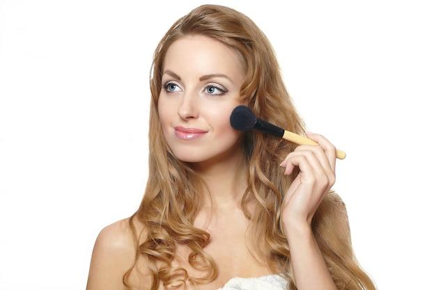 Retrato do close-up de jovem mulher bonita aplicar maquiagem
