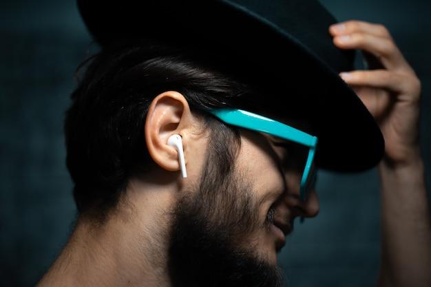 Retrato do close-up de jovem, ouvir música com fones de ouvido sem fio, usando óculos escuros azuis e chapéu preto, em fundo escuro.