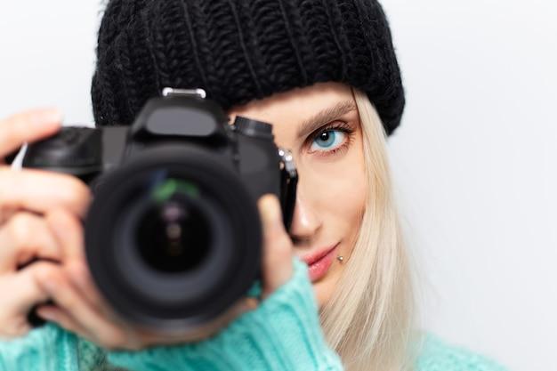 Retrato do close-up de jovem tirando foto na câmera dslr contra uma parede branca.