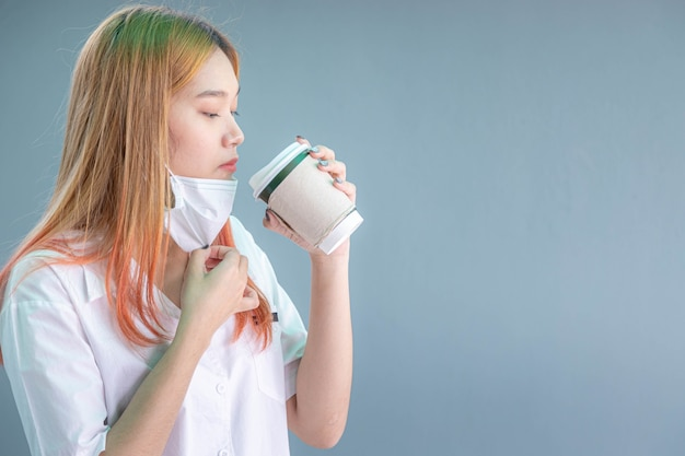 Retrato do close-up de menina bonita com máscara facial, segurando uma xícara de café de papel, isolado no fundo cinza.