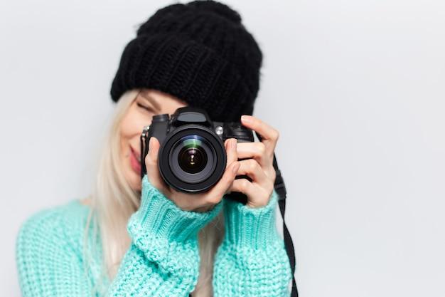 Retrato do close-up de menina bonita loira tirando foto na câmera moderna, vestindo suéter azul e chapéu preto sobre fundo branco.