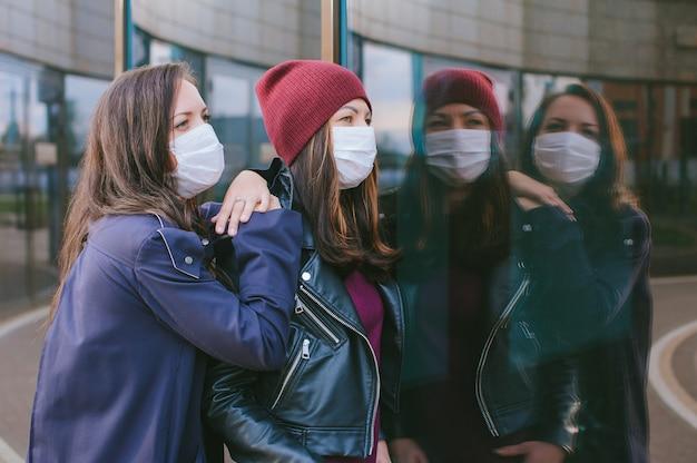 Retrato do close-up de meninas com máscaras médicas. no contexto de um edifício de vidro com reflexos. conceito sobre o tema viros.