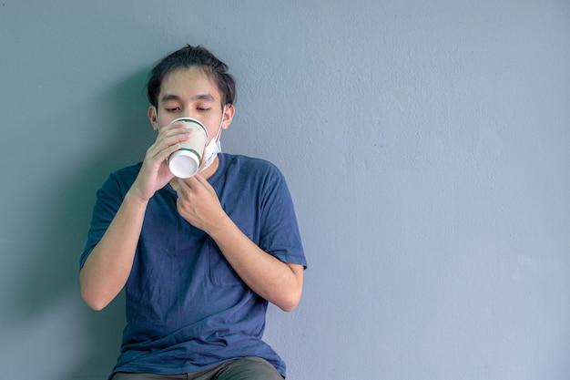 Retrato do close-up de menino usando máscara facial segurando uma xícara de café de papel, isolado no fundo cinza.