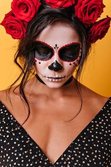 Retrato do close-up de morena com coroa de rosas, abaixando a cabeça humildemente. mulher com maquiagem de caveira abaixou seu leve