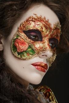 Retrato do close-up de mulher bonita no vestido vintage e uma máscara no rosto.