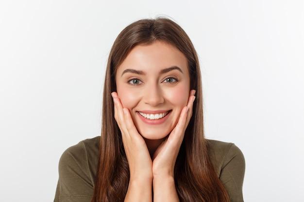 Retrato do close-up de mulher bonita surpresa, segurando sua cabeça com espanto e boca aberta. sobre parede branca