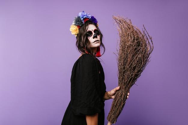 Retrato do close-up de mulher com olhar suspeito em máscara de caveira. senhora de vestido preto segurando a vassoura.