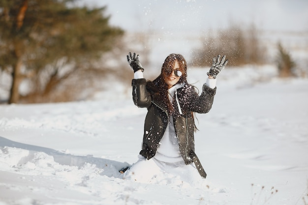Retrato do close-up de mulher de jaqueta preta. mulher de pé em uma floresta em um dia de neve.