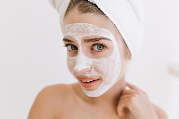 Retrato do close-up de mulher jovem e bonita com toalhas depois de tomar banho fazer máscara cosmética no rosto.