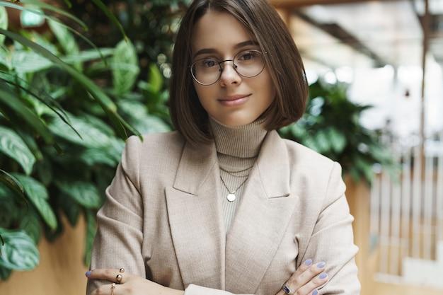 Retrato do close-up de mulher jovem e bonita elegante, olhar profissional, cruzar as mãos no peito e sorrindo confiante câmera, usar óculos, perto da recepção ou do escritório, discutir negócios.