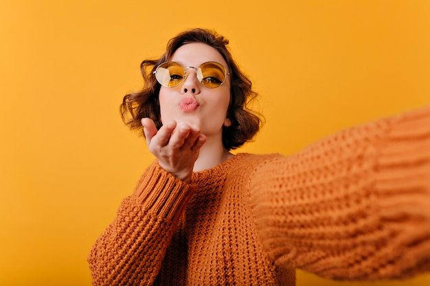 Retrato do close-up de mulher jovem e bonita em suéter macio enviando beijo no ar. menina na moda com cabelos ondulados, fazendo selfie com expressão facial inspirada.