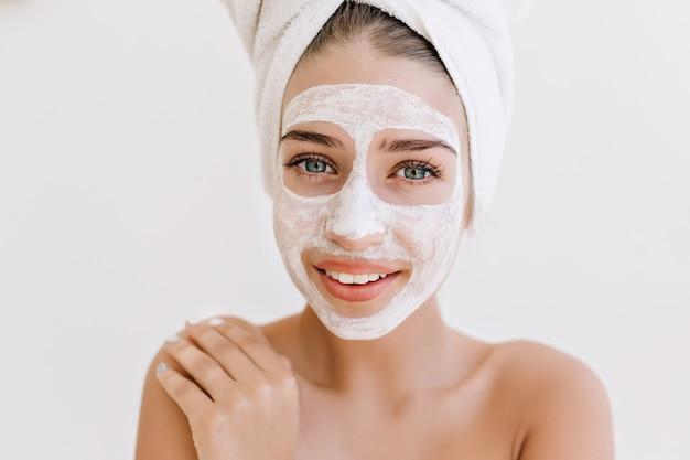 Retrato do close-up de mulher jovem e bonita sorrindo com toalhas depois do banho fazer máscara cosmética no rosto.