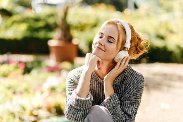 Retrato do close-up de mulher ouvindo música de bom humor, vestida com uma camisola de malha cinza.