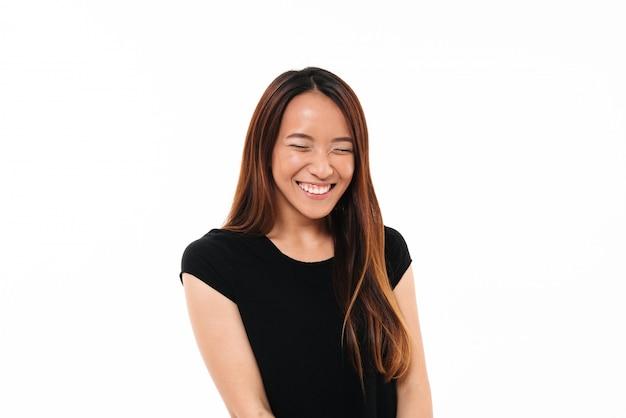 Retrato do close-up de rir mulher asiática atraente com os olhos fechados, isolado no branco