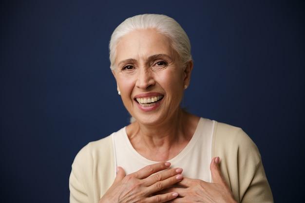 Retrato do close-up de rir mulher madura, segurando as mãos no peito